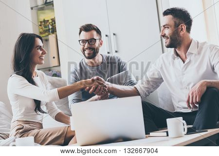 Welcome on board! Three young cheerful business people sitting together at the desk while man and woman shaking hands