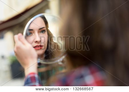 Young Woman Looking At Herself In A Little Mirror