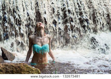 elegant brunette woman enjoying a waterfall outdoors