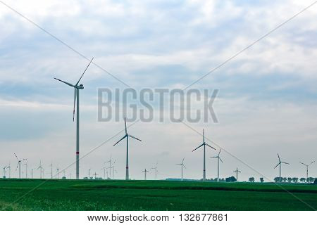 Lots of windmills on a green field.Windmills for electric eco power production.Big windmills for renewable electric energy production.