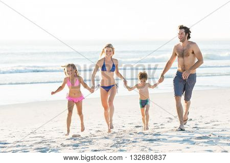 Smiling family running with holding hands at beach. Happy family having fun together on beautiful sunny beach. Young family on beach vacation.
