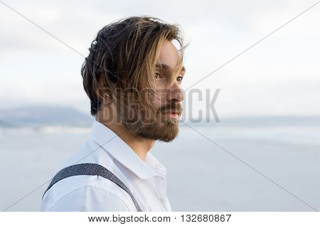 Young man thinking at the beach. Handsome young serious man looking away and thinking about the future. Thoughtful guy looking at the sea on the beach.