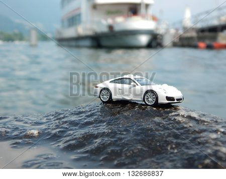 A small, white car defies the waves of Lake Maggiore.