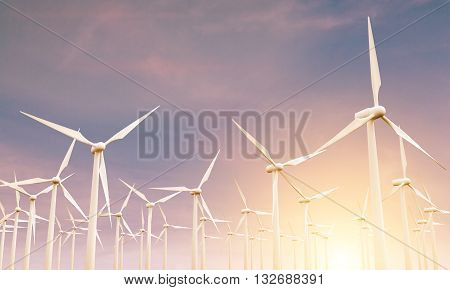 Numerous wind mills in the sky at sunset. 3D Rendering
