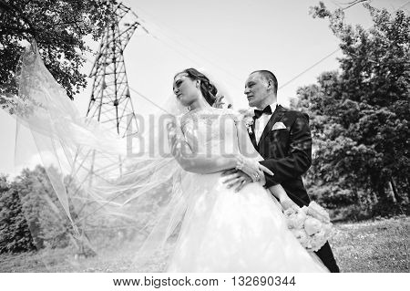 Fashionable Wedding Couple Background Electrical Tower, Long Veil Of Bride. B&w Photo