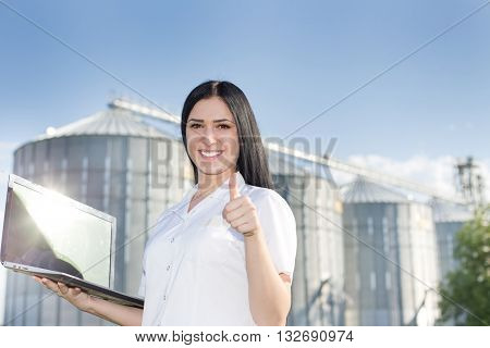 Woman Agronomist In Front Of Silo With Thumb Up