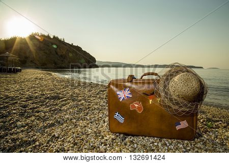 Vintage suitcase with flag stickers and a straw hat placed on the beach with peacefull sea during sunrise on Thassos island in Greece