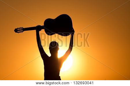 Silhouette Of Girl With Raised Guitar