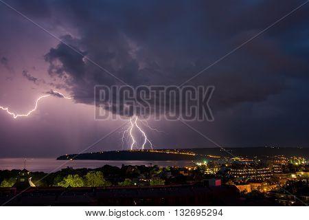 Photo of beautiful powerful lightning over big city, zipper and thunderstorm, Varna. Bulgaria