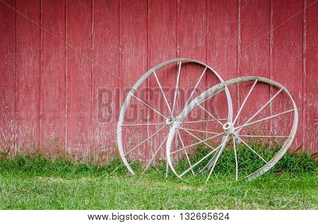 Wagon wheels against a red barn background