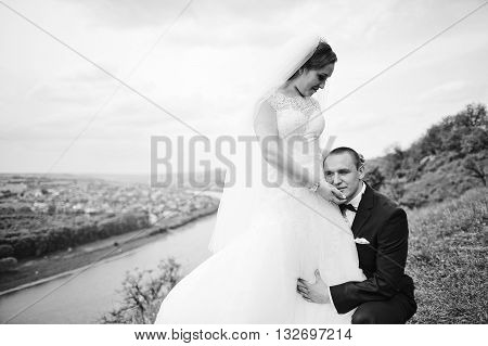 Gorgeous Wedding Couple On The Hill With River And Beautiful Landscape, Groom Sits Near Bride. B&w P