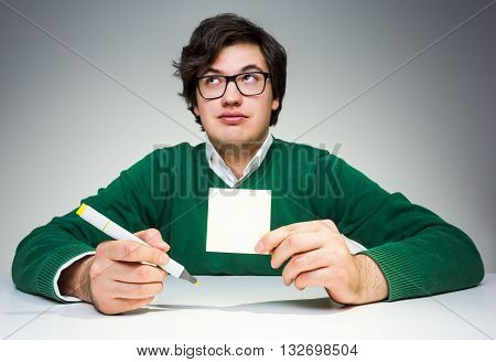Young man in green pullover sitting at white desk with blank paper sticker and marker in hand raising eyebrows and looking up