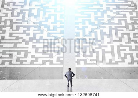 Success concept with businessman and difficult maze divided into two parts on concrete ground