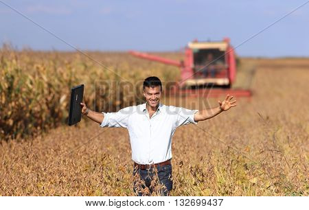 Farmer With Combine Harvester In Soybean Field