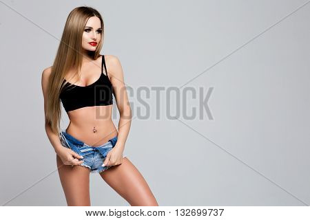 closeup Portrait of a slender shapely young woman in a denim dress with long straight hair. The Studio, grey background