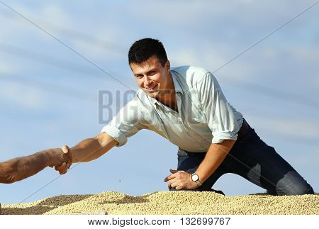 Businessman Shaking Hands With Worker On Soybean Heap