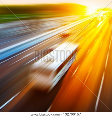 Motion blurred image of driving bus during sunset.