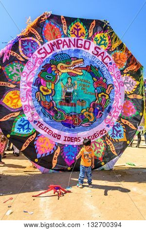 Sumpango Guatemala - November 1 2015: Boy plays in front of kite at giant kite festival on All Saints' Day to honor spirits of dead.