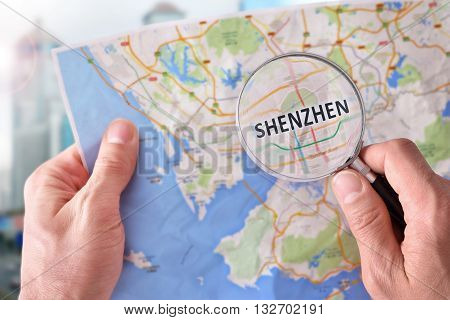Man Consulting A Map Of Shenzhen With A Magnifying Glass