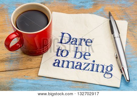 Dare to be amazing - motivational handwriting on a napkin with a cup of coffee