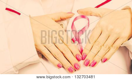 Awareness of breast cancer. Close up of female doctor hands make heart on pink ribbon symbol sign. Help and charity. Filtered.