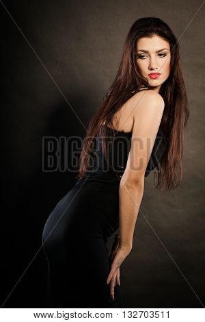 Party celebration concept. Magnificent long hair woman red lipstick wearing black evening dress on dark