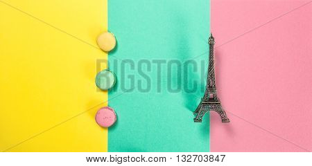 Macaroon cookies on pink green yellow colored background. Macarons french cake. Eiffel tower Paris. Minimal concept