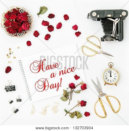 Flat lay with sketchbook red rose vintage camera scissors on white background. Red flowers. Have a nice Day!