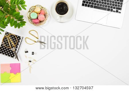 Feminine office desk workplace. Coffee cookies laptop computer and green plant on white table background. Top view. Flat lay