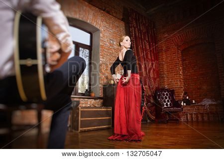 Young Woman Dancing Flamenco And A Man Playing The Guitar