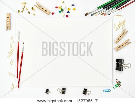 Sketchbook brushes paper office supplies on white background. Flat lay. Creative art concept