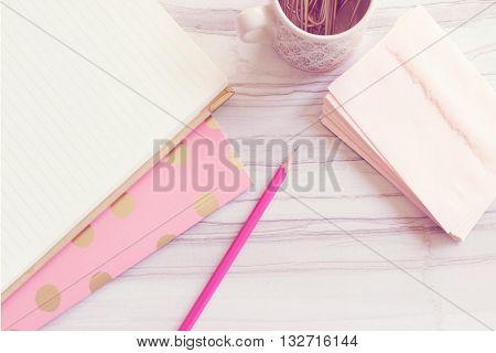Over head desktop, blank notebook, pink folder, pink envelopes, paper clips