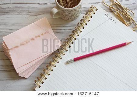 Over head view of to do list on blank paper, marble, pink envelopes, pink pencil, and gold paperclips