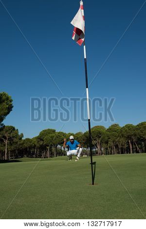 golf player aiming shot with club on course at beautiful sunny day