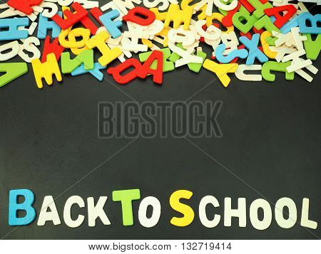Colorful alphabet of back to school on wooden wood background with copy space at middle for text.