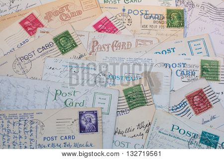 Collage of old postmarked postcards for background.