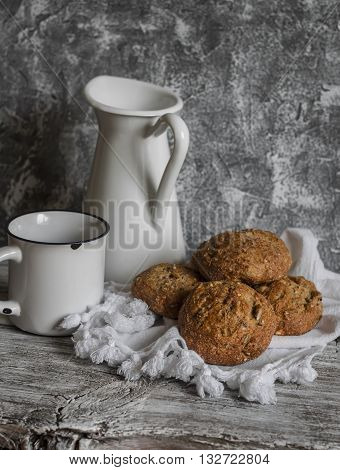 Multi seed whole grain rolls and a enamel jug and mugs on a grey wooden rustic background
