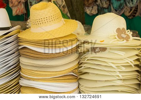 Collection of handmade straw hats on stall at the bazaar summer fashion head protection