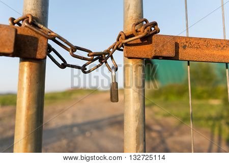 A fence locked wirh a chain and secured by a padlock photographed in horizontal format
