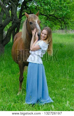 Young beautiful woman in a long skirt hugs muzzle of bay horse