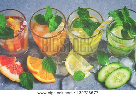 Refreshing summer drinks water with ice and lemon, orange, grapefruit and cucumber, tinted