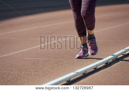 Athletic woman running on the track field