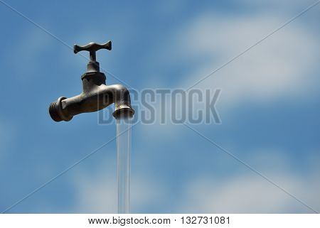 Old water faucet with running water and a blue sky.Without power and water supplies