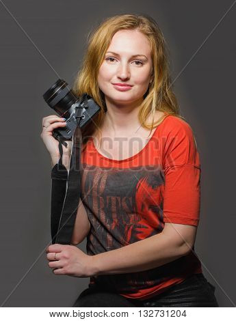 Red-haired pretty girl with the camera in a red T-shirt on a gray background looks in the picture sitting portrait sdudiyny