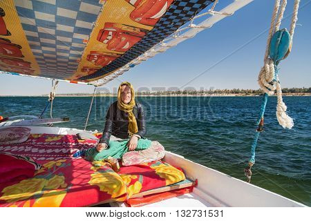 Female tourist eating snack during felucca trip on the Nile.