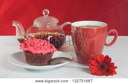 Red cup of tea, glass teapot, red gerbera flower and red velvet muffin with cream rose topping on White and red background