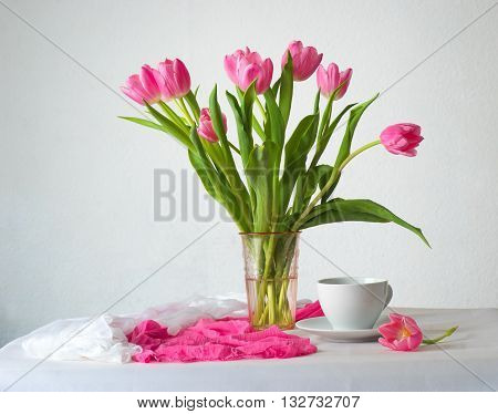 Still life with bunch of pink tulips on white background and white table with cup of coffee