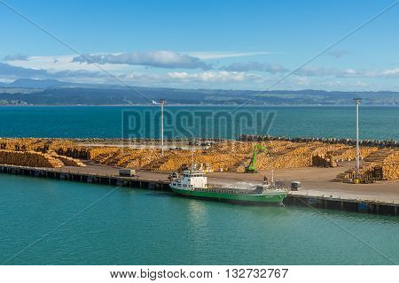 Wellington New Zealand - November 18 2014: NZ export logs all stack up wait for the next ship to come in at Port of Wellington New Zealand. Cargo ship Anatoki foreground and timber ready for export.