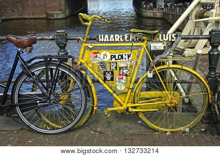 AMSTERDAM, NETHERLANDS - MAY 3, 2016: Amsterdam scene with vintage yellow bicycle on canal bridge Amsterdam Netherlands.