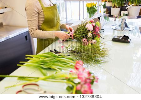 people, business, sale and floristry concept - close up of florist woman making bunch at flower shop